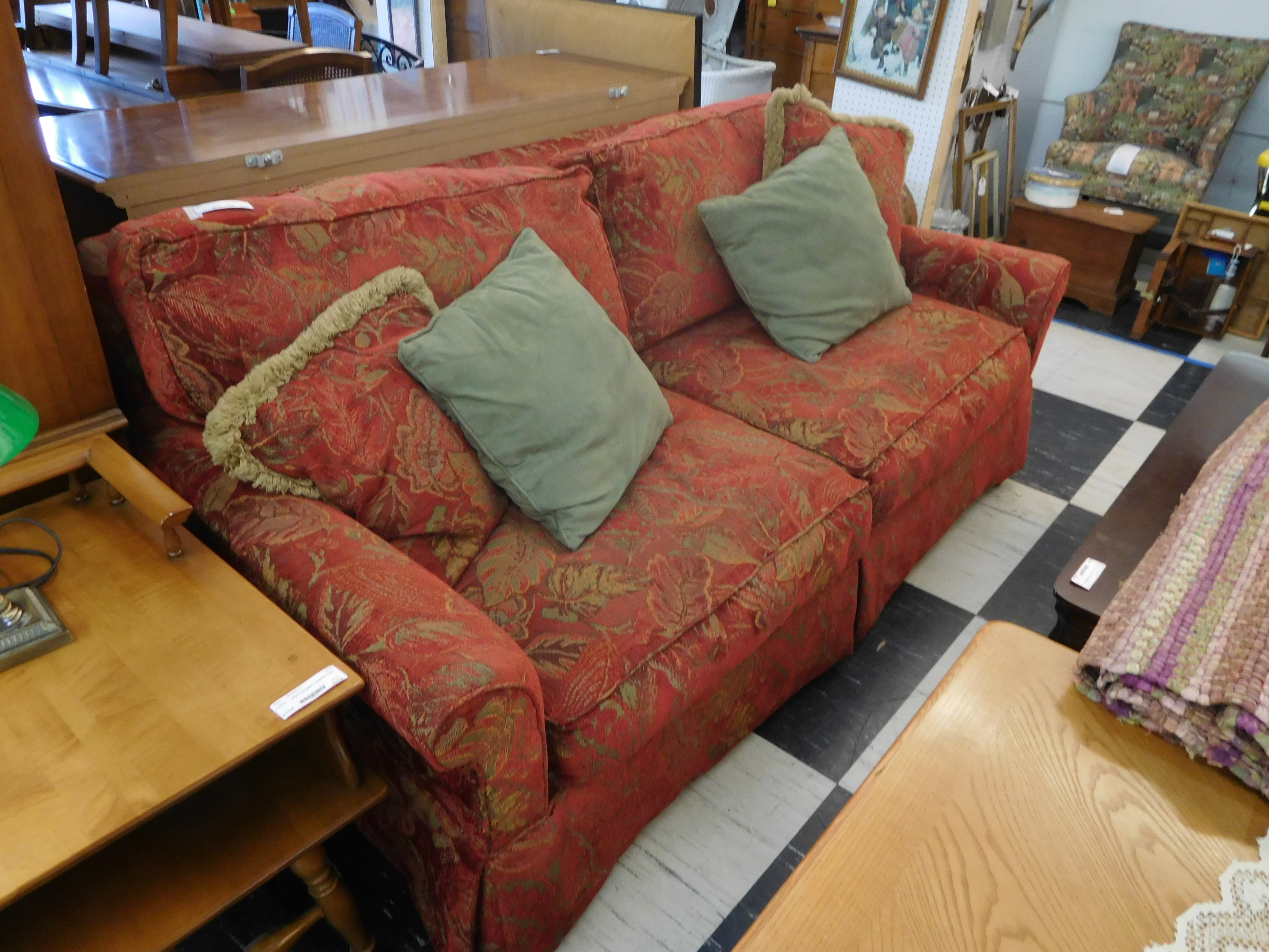 Reddish Sofa with Leaf Patterned Upholstery and Matching Pillows