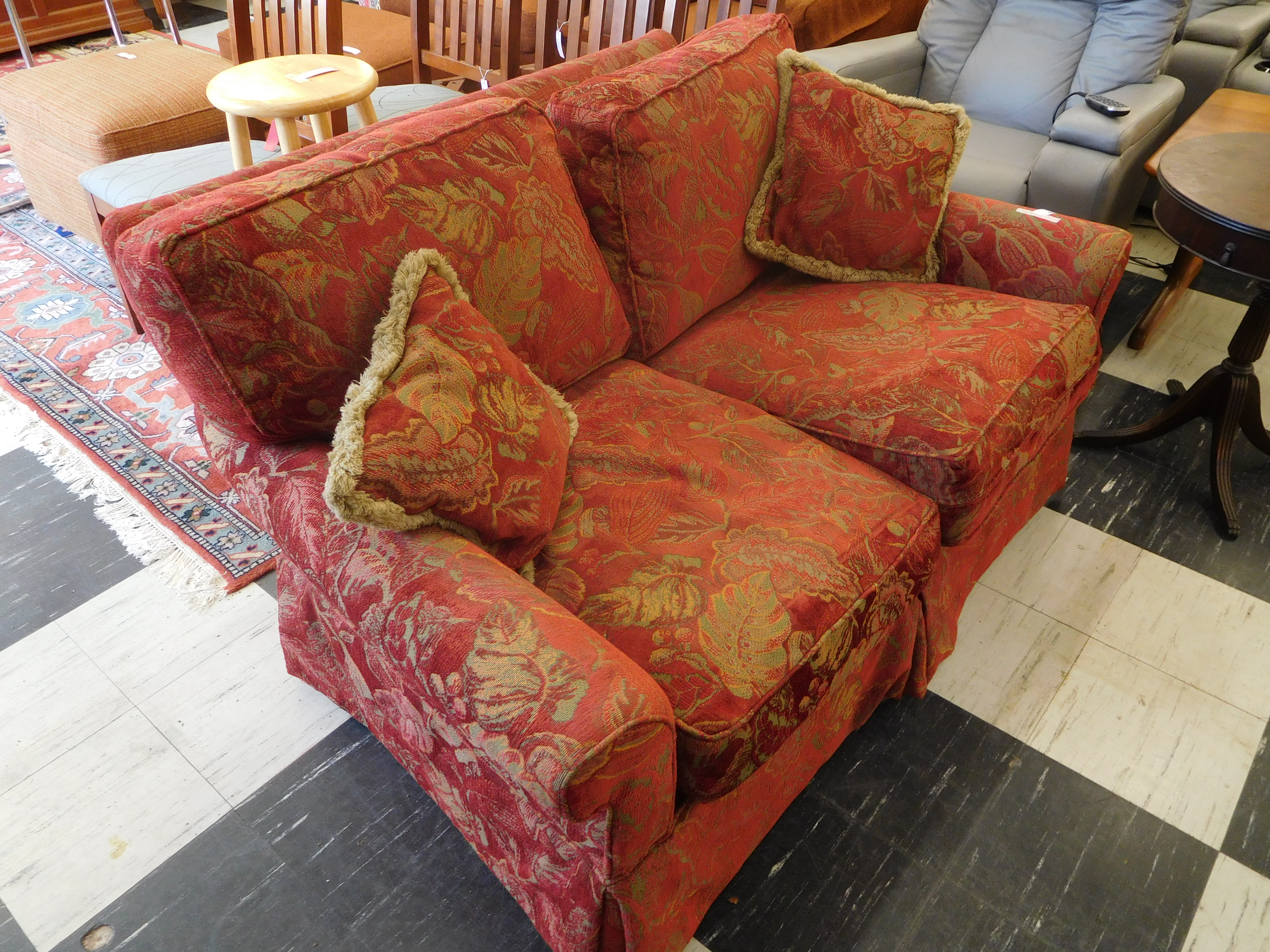 Reddish Love Seat with Leaf Patterned Upholstery and Matching Pillows